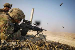 A U.S. soldier from the 3rd Cavalry Regiment is watched as he fires a squad automatic weapon during a training mission near forward operating base Gamberi, in the Laghman province of Afghanistan December 15, 2014. REUTERS/Lucas Jackson.